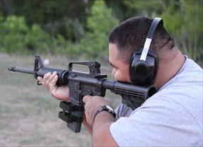 Man with ear protectors aims a rifle